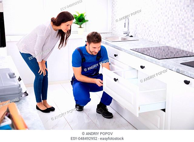 Woman Looking At Male Handyman Installing Door Of Drawer In The Kitchen
