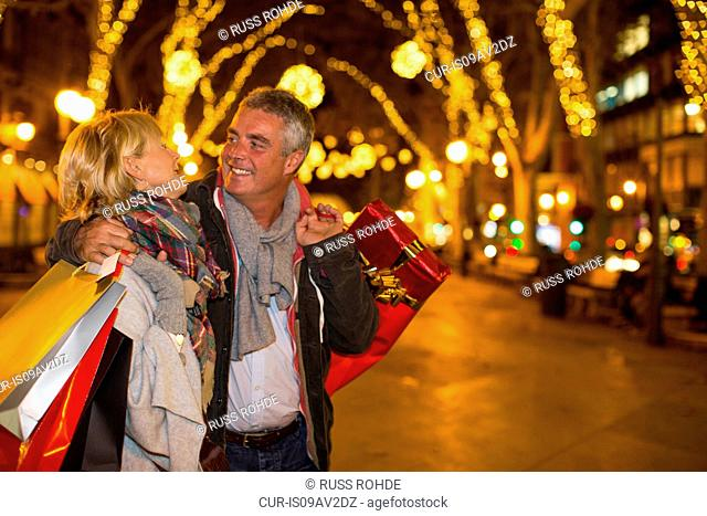 Mature couple carrying xmas shopping on tree lined avenue, Majorca, Spain