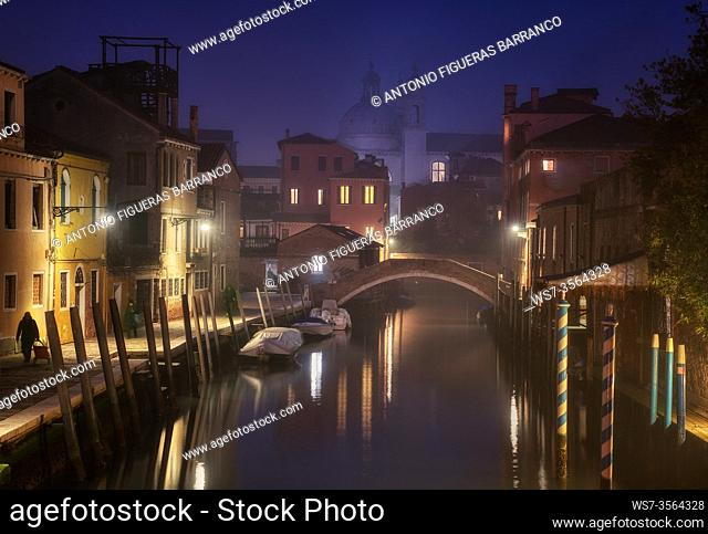 Dusk among mists on a canal in Venice, with the Church of Santa Maria del Rosario in the background