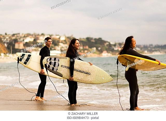 Three friends standing in sea, holding surfboards, preparing to surf