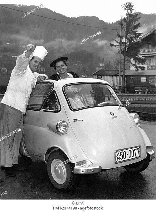 """A chef shows a driver in a BMW Isetta the way. The Bavarian engine works have built an engine coupé called """"""""Isetta"""""""". - /Germany"""