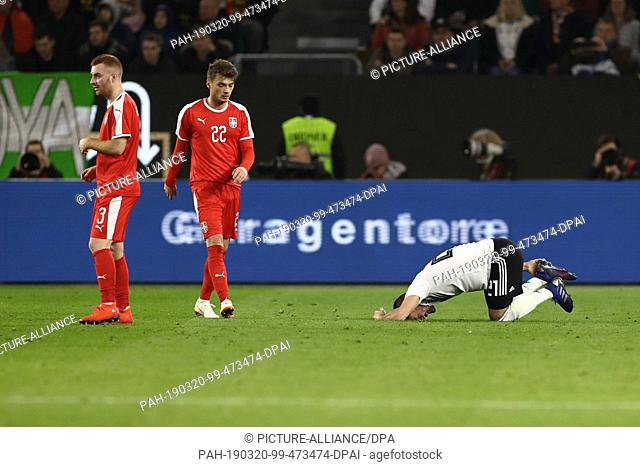 20 March 2019, Lower Saxony, Wolfsburg: Soccer: International match, Germany - Serbia in the Volkswagen Arena. Ilkay Gündogan (r-l) from Germany is painfully...