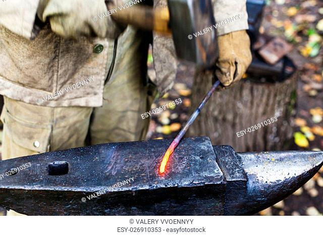 Blacksmith hammering red hot iron rod on anvil in outdoor rural smithy