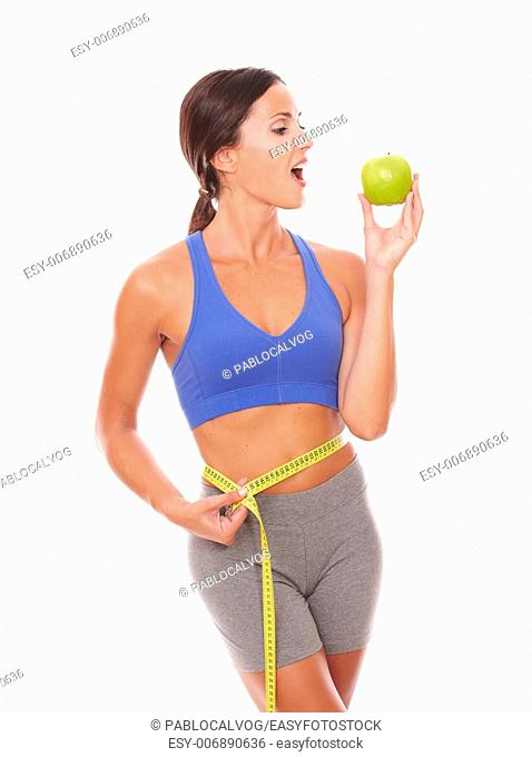 Latin young woman in sport clothing biting an apple to lose weight on isolated background