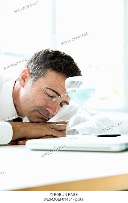 Businessman sleeping on table in office with hourglass
