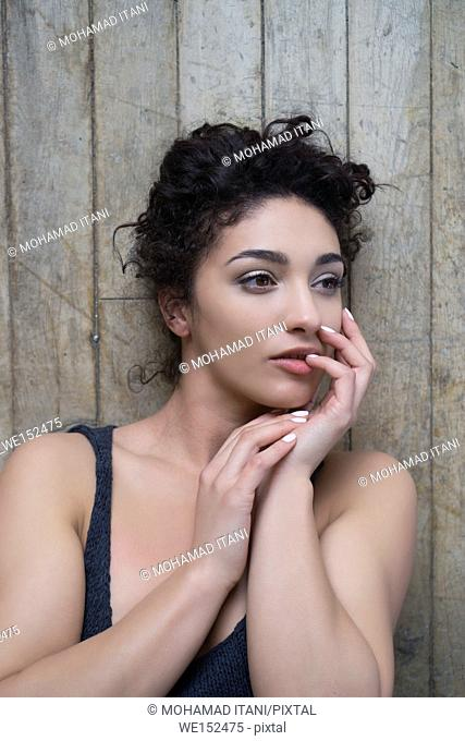 Pensive young woman laying down on the floor hands touching face looking away