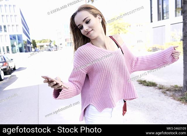 Young woman on the street, using smartphone. Munich, Germany