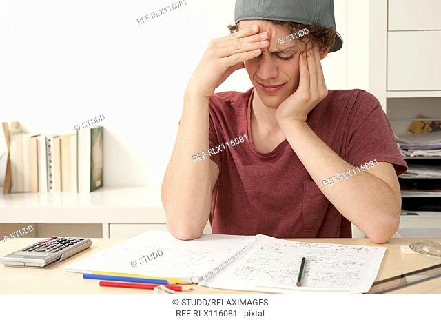 Teenager under stress while doing school work