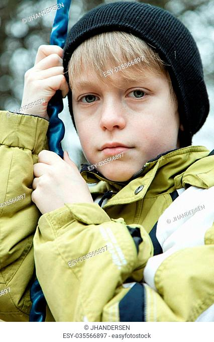 Low angle close up view on calm blond male child in coat and black knitted hat hanging on to chain on swing outdoors
