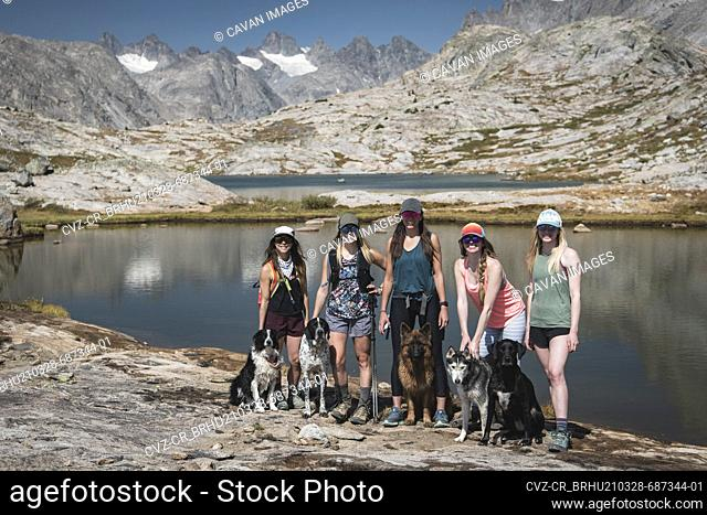 Smiling female friends with dogs standing at Titcomb Basin on sunny day