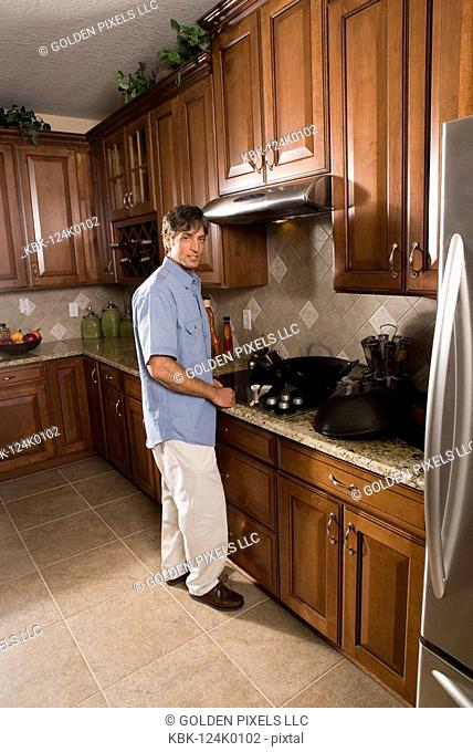Portrait of a mid adult man standing at kitchen stove