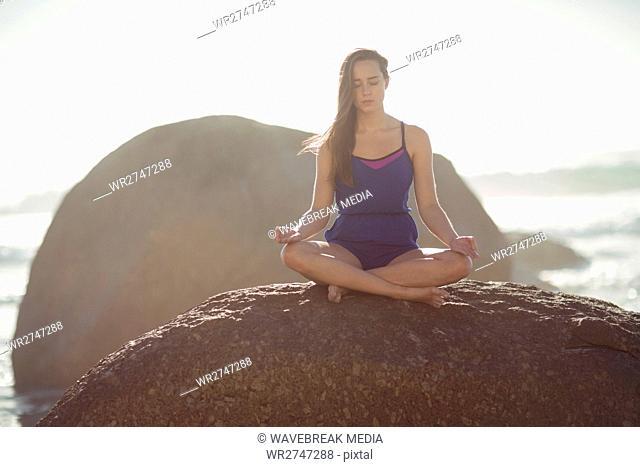Beautiful woman performing yoga on rock