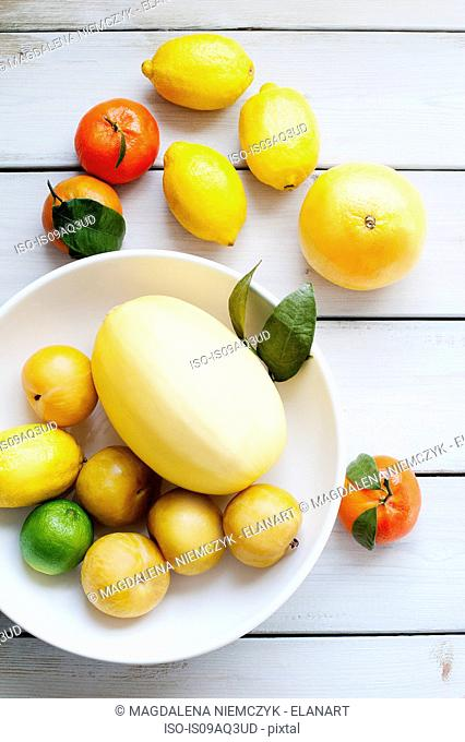 Top view of various citrus fruits in a white bowl on table