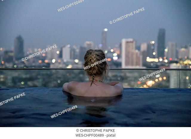 Thailand, Bangkok, back view of woman bathing in Infinity Pool looking at skyline