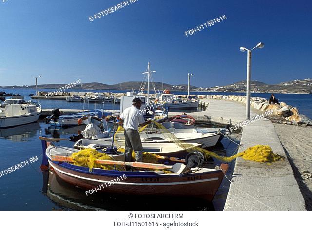 Paros, Greek Islands, Parikia, Cyclades, Greece, Europe, Fisherman pulling net onto fishing boat docked in the harbor of Parikia on Paros Island on the Aegean...