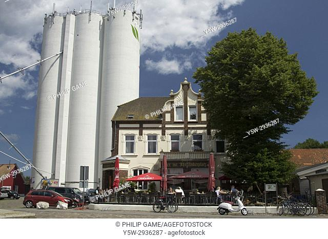 Silos tower over a tavern in the seaside village of Hafen Burgstaaken, Fehmarn Island, Holstein, Germany
