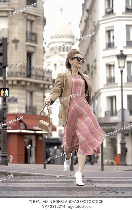 fashionable blogger woman running at street in front of touristic sight Basilica Sacré-Cœur, during fashion week, in city Paris, France