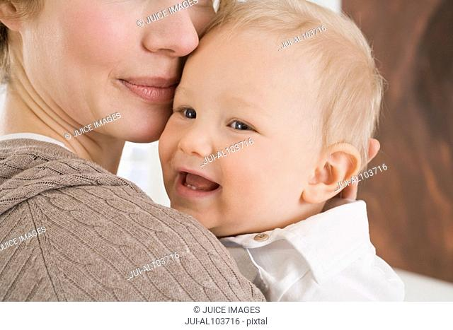 A mother holding her young son in her arms, close-up