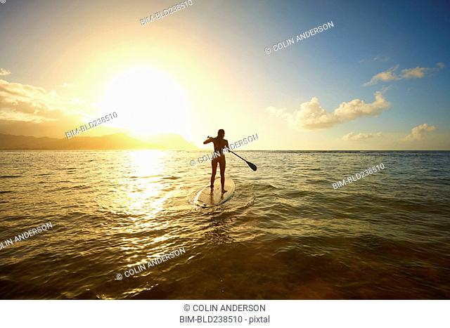 Silhouette of Mixed Race woman standing on paddleboard