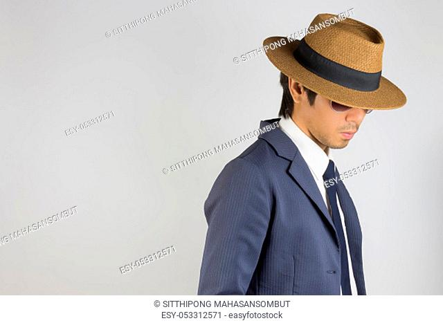 Young Asian Portrait Businessman in Navy Blue Suit Wear Hat and Sunglasses Looking Below at Right Frame on Grey Background