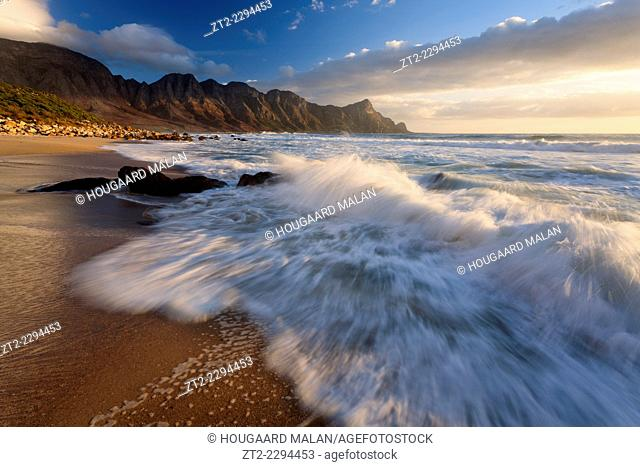 Landscape photo of a wave washing over a beach under dramatic sunset light. Kogelbay beach, Western Cape, South Africa