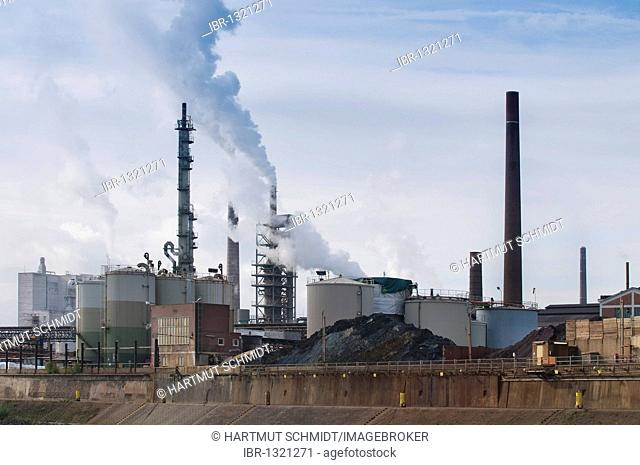 Duisburg Port, large oil storage tanks, coal heaps and smoking industrial chimneys in the evening light, North Rhine-Westphalia, Germany, Europe