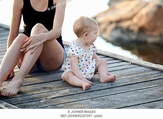 Baby girl and woman sitting on pier