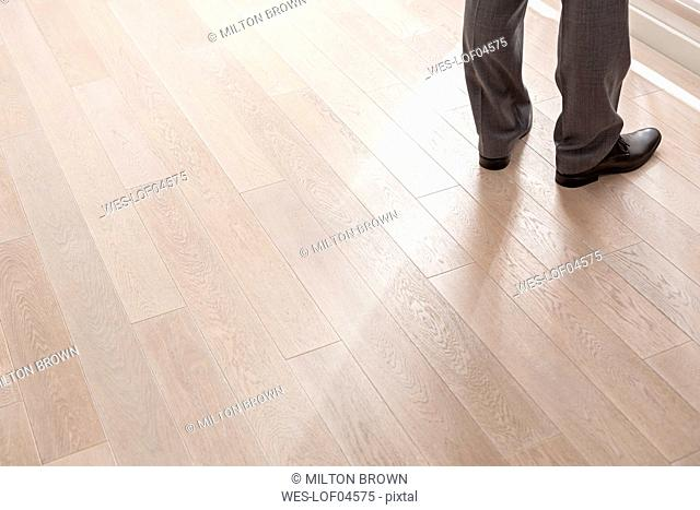 Feet of businessman on wooden floor