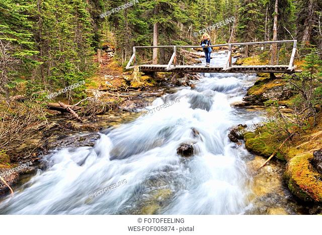 Canada, British Columbia, Yoho Nationalpark, Woman on footbbridge over Cataract Brook