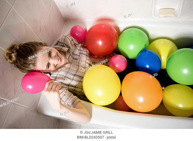 Smiling woman sitting in bathtub with multicolor balloons