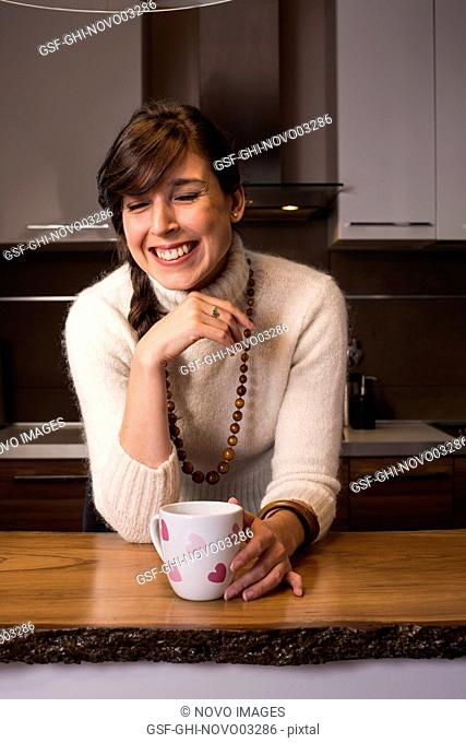 Laughing Woman with Cup with Pink Hearts in Kitchen