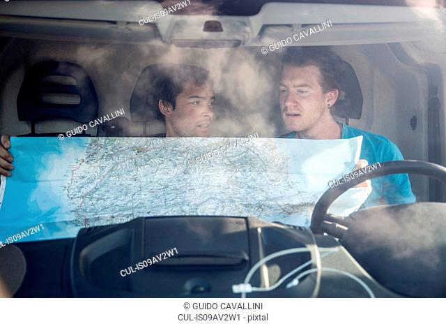 View through windscreen of young men in recreational van looking at map, Costa Smeralda, Sardinia, Italy