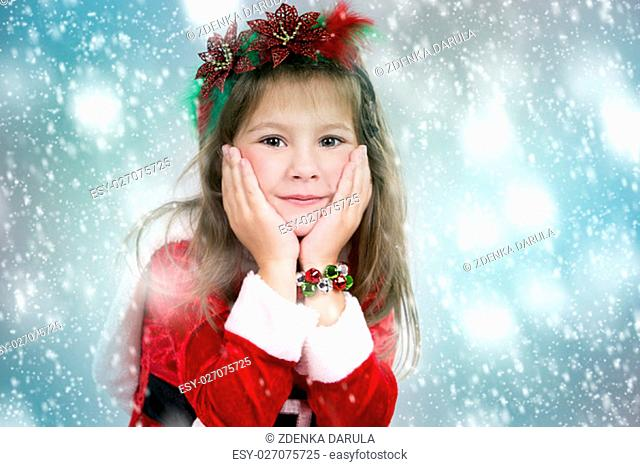 cute girl wearing christmas outfit on snowy background