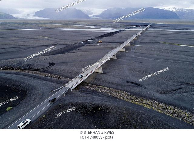Aerial view of vehicles on bridge against mountains, Iceland