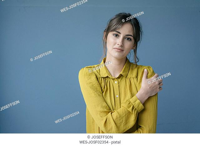 Portrait of a young woman wearing a yellow blouse