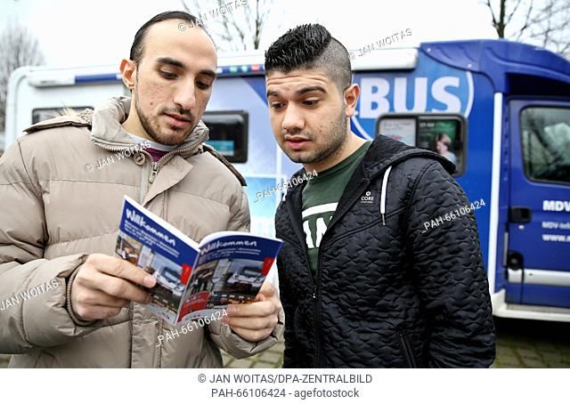 Refugees Ahmad Zino (L) and Bankin Mostafa look at the new flyer by the central German transport association (MDV), which is also available in Arabic and...