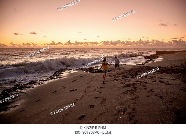 Boy and sister running on beach at sunrise, Blowing Rocks Preserve, Jupiter Island, Florida, USA