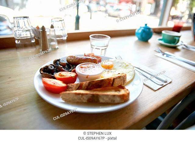 Full English breakfast on window seat counter in cafe