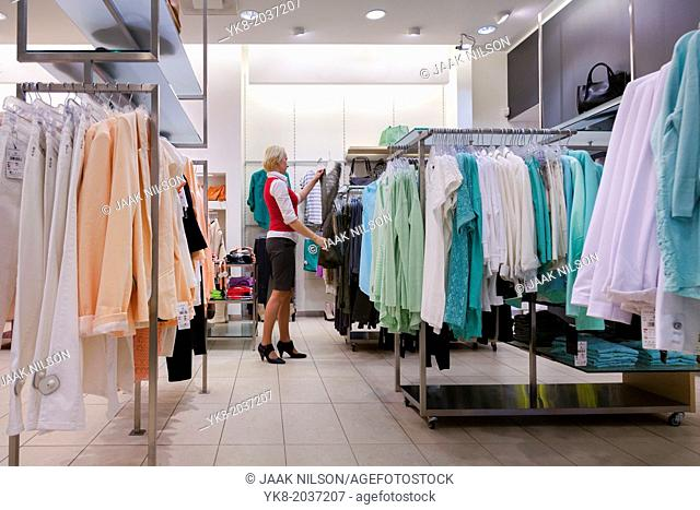 Woman, buyer in fashion shop aisle. Retail outlet and fashion shop interior. Shopping