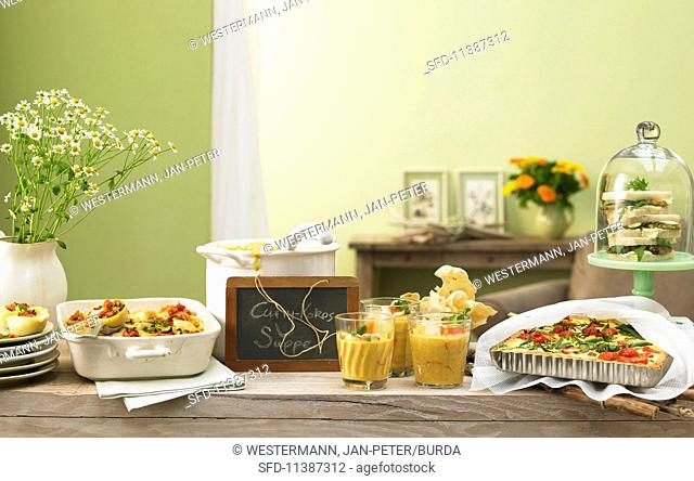 A summer buffet with various dishes and a slate