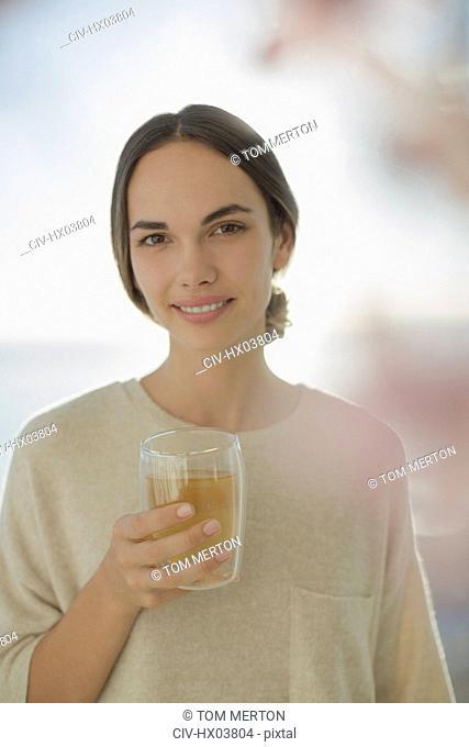 Portrait smiling brunette woman drinking juice