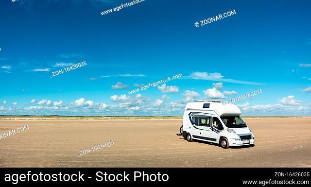Camping Car RV Motorhome standing on empty sand beach panorama on sunny day. Romo Bilstrand, Lakolk Strand, Denmark
