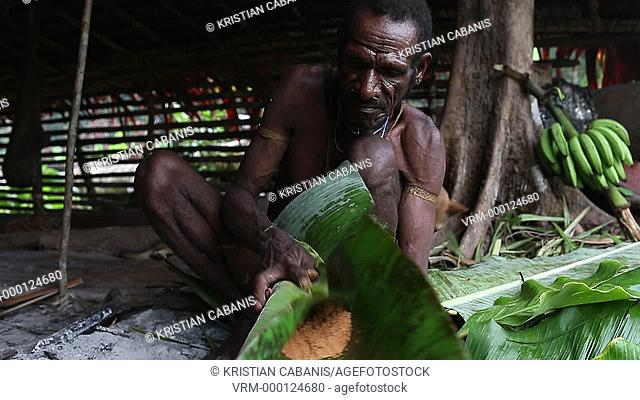 Woman from the Kombai tribe making a loave from Sago in banana leaf, Papua, Indonesia, Southeast Asia