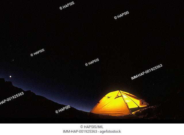 Aurora Borealis over illuminated tent  Alaska, United States, North America