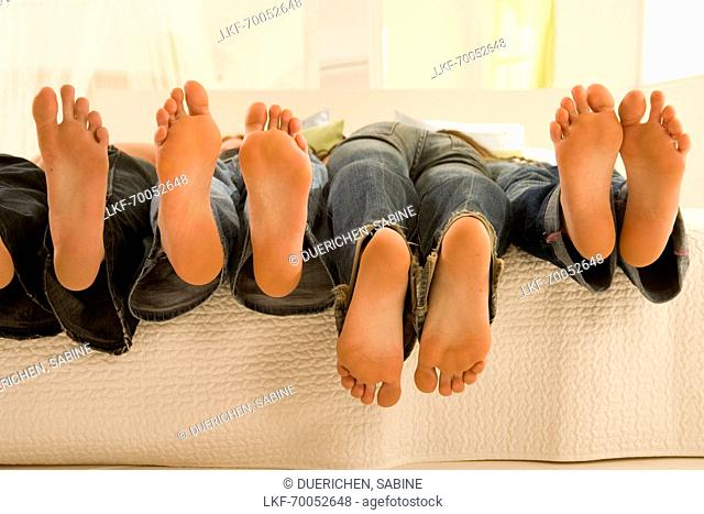 Teenage girls feet hanging off of the bed