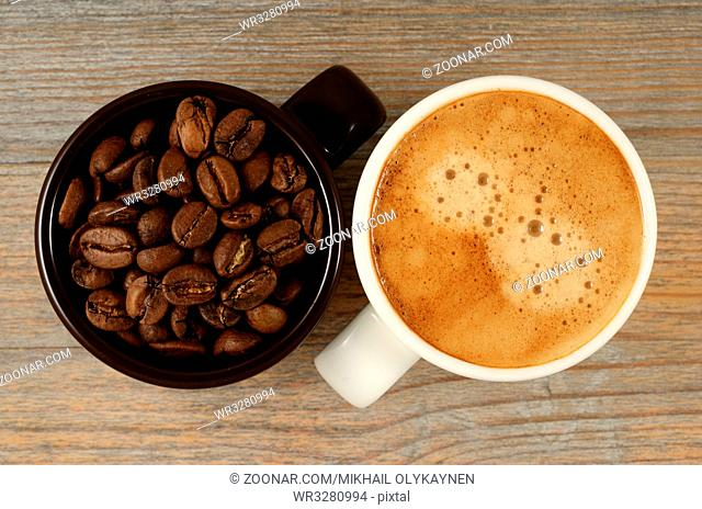 two cups of coffee and beans on wood
