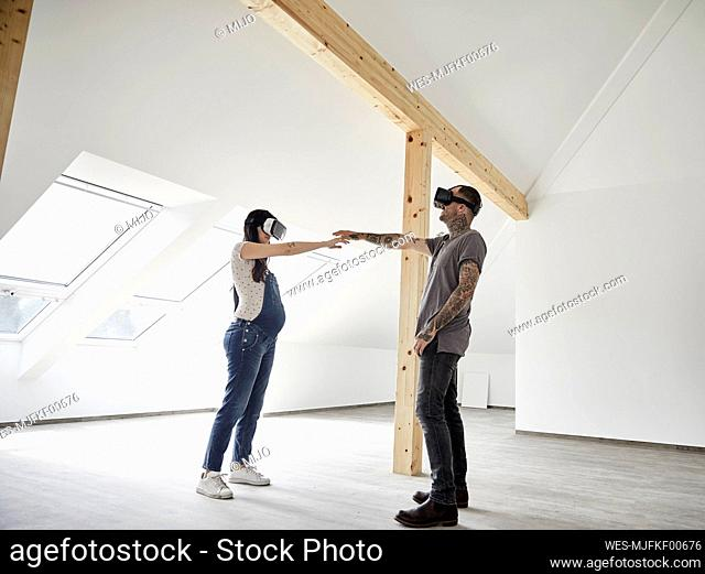 Couple pointing towards each other while wearing virtual reality simulator