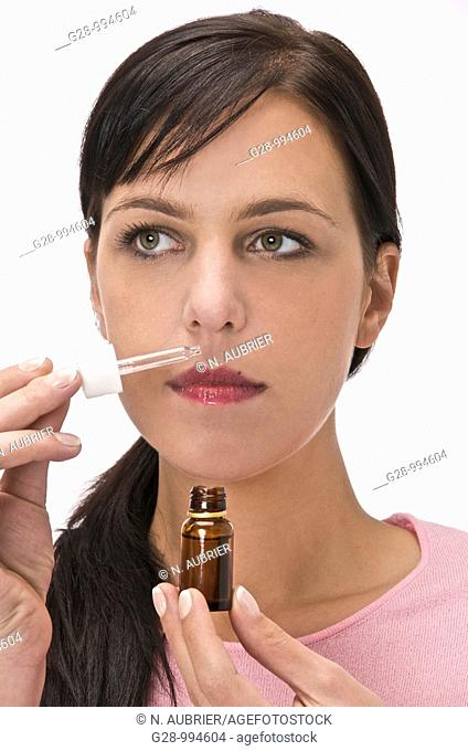 young woman smelling essential oil with a small bottle and a dropper
