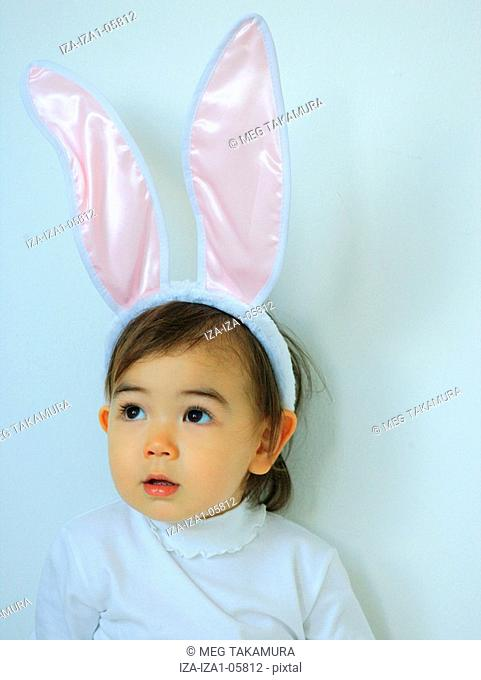 Close-up of a baby girl wearing a rabbit costume