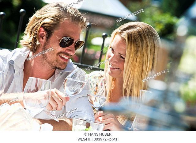 Austria, Salzburg County, Couple sitting on terrace in hotel garden